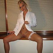 horny blonde milf posing for adult photos while smoking a cigarette