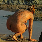 Spying mature woman at the beach early morning covered in mud