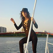 Friends sexy wife posing on a boat while on holiday wearing a catsuit