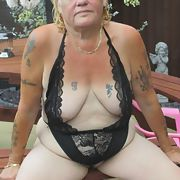 Sandy in black teddy showing her ample assets