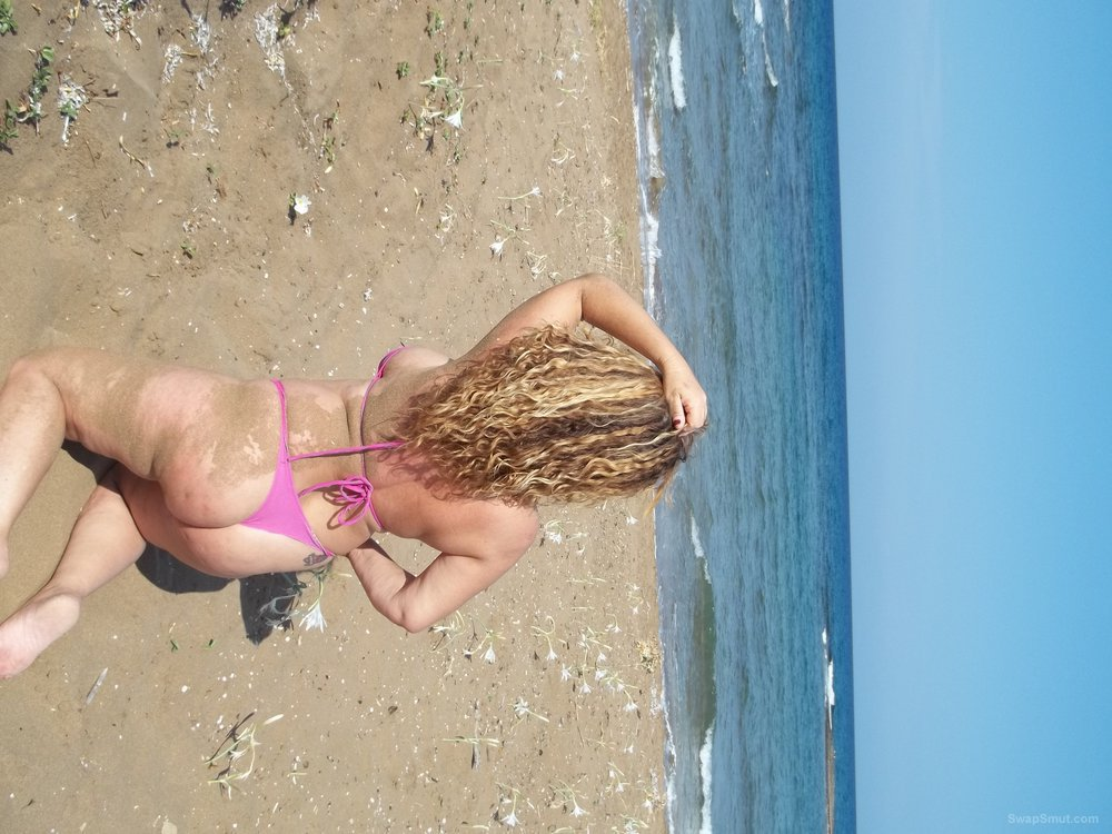 Sexy 32 year old wife in bikini on the beach having photos taken