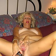 Mature blonde masturbating with a bottle and wearing tight jeans