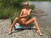 Blonde bimbo inserts a huge glass dildo in her shaved pussy in public